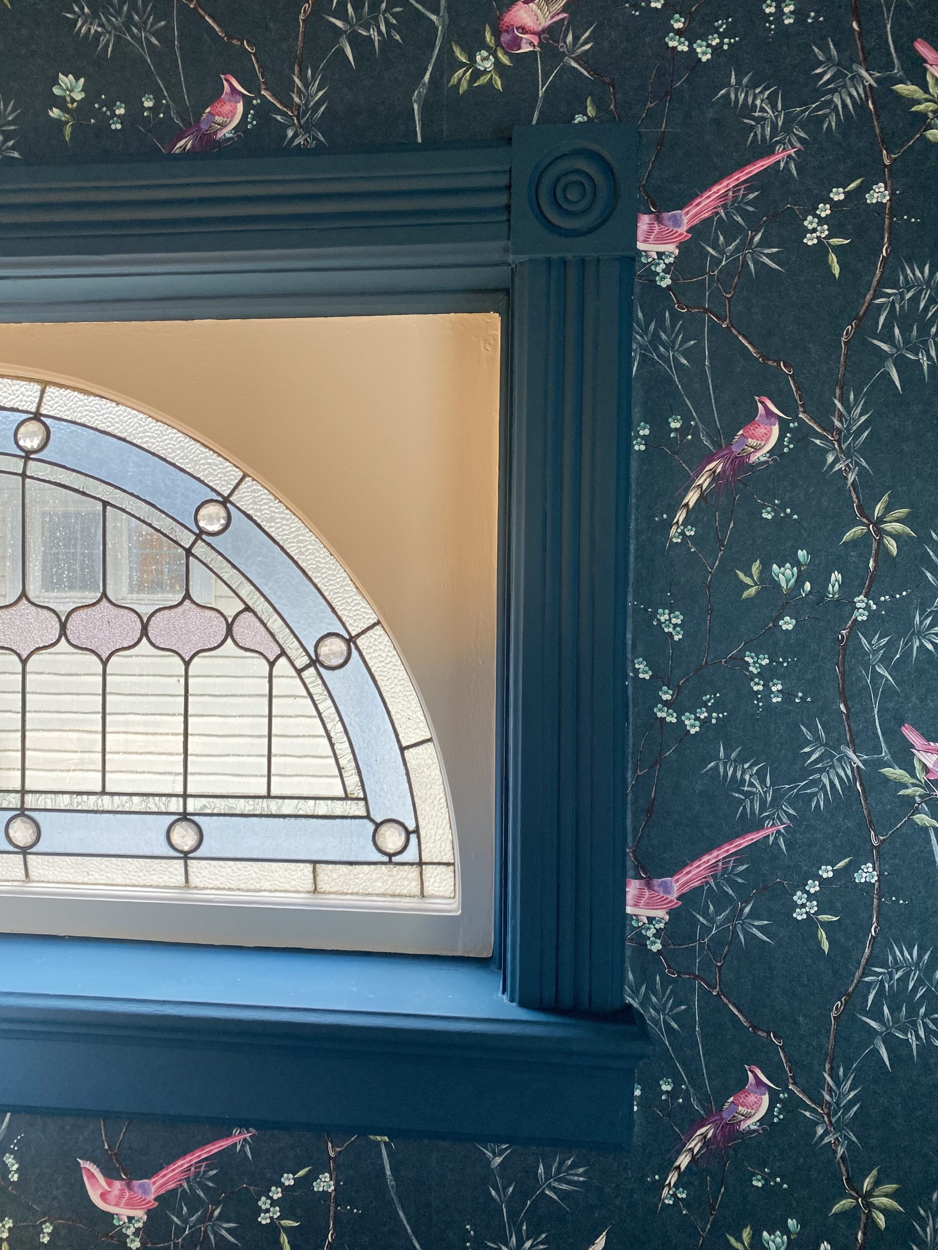 Teal wallpaper and stained glass window inside interior designer Heather Prestanski's victorian Windsor home