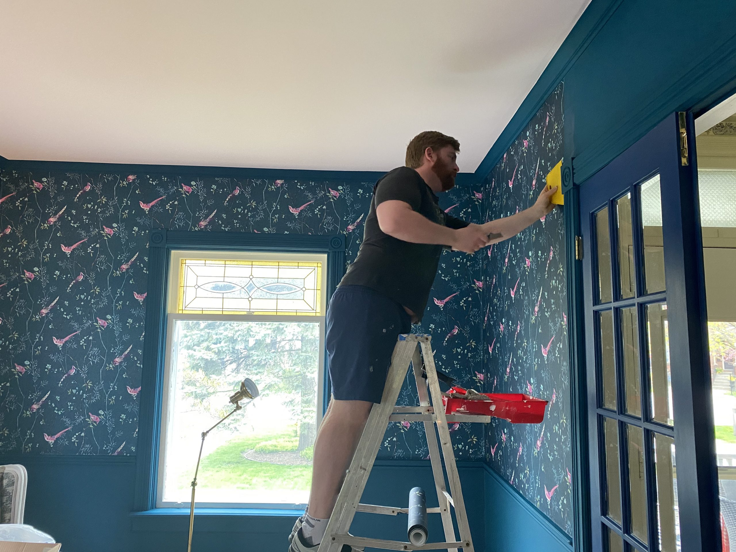 Kyle is smoothing out the wallpaper chosen by interior decorator Heather in their Windsor home