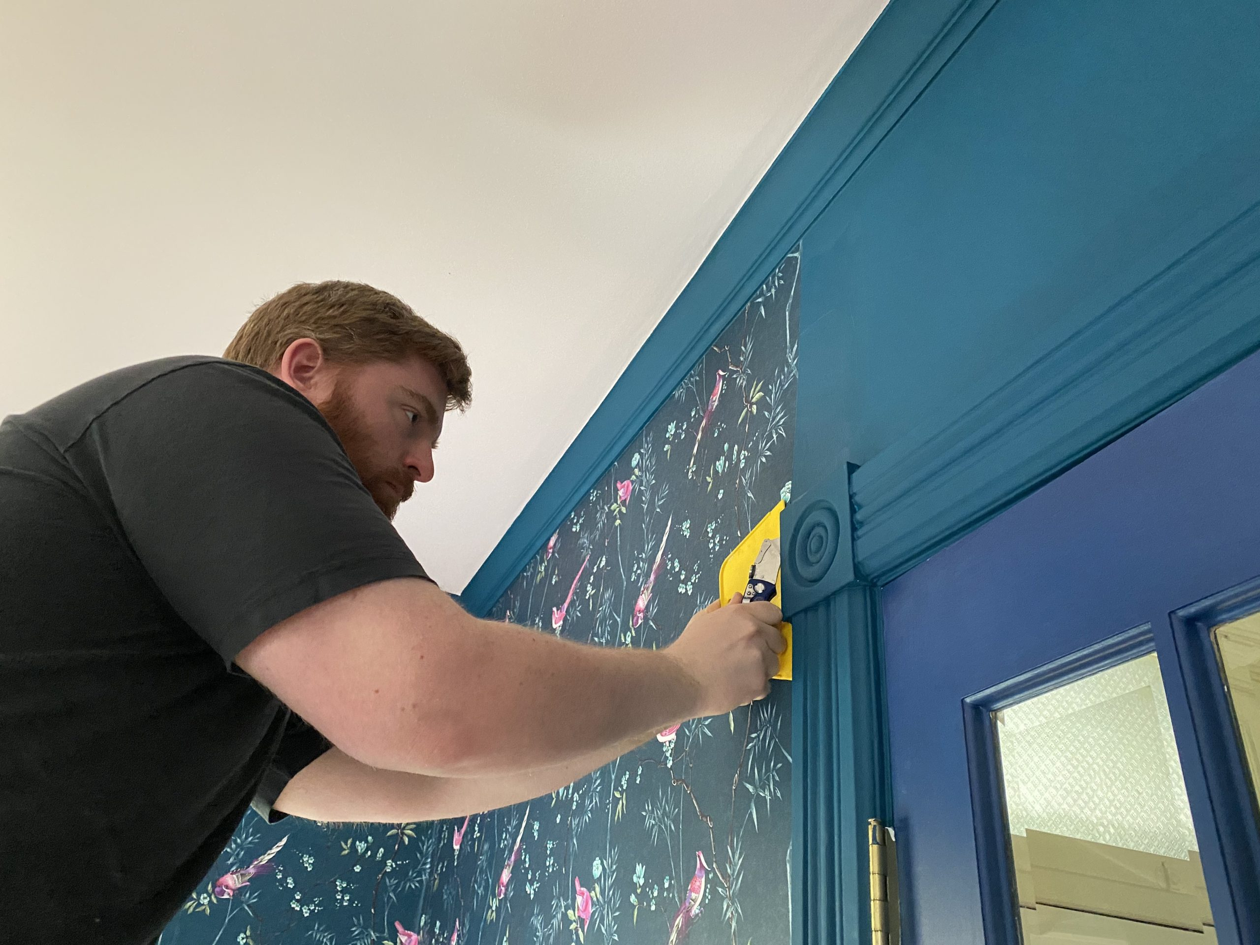 Kyle making the tricky cuts while installing the teal wallpaper in our Chatham Victorian home