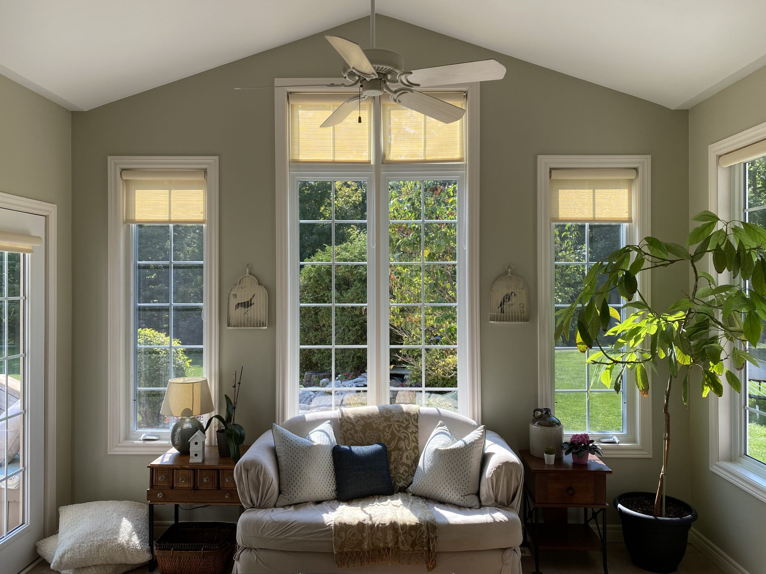 Transitional lakeside retreat sunroom in Chatham-Kent with custom drapery and colourful accents