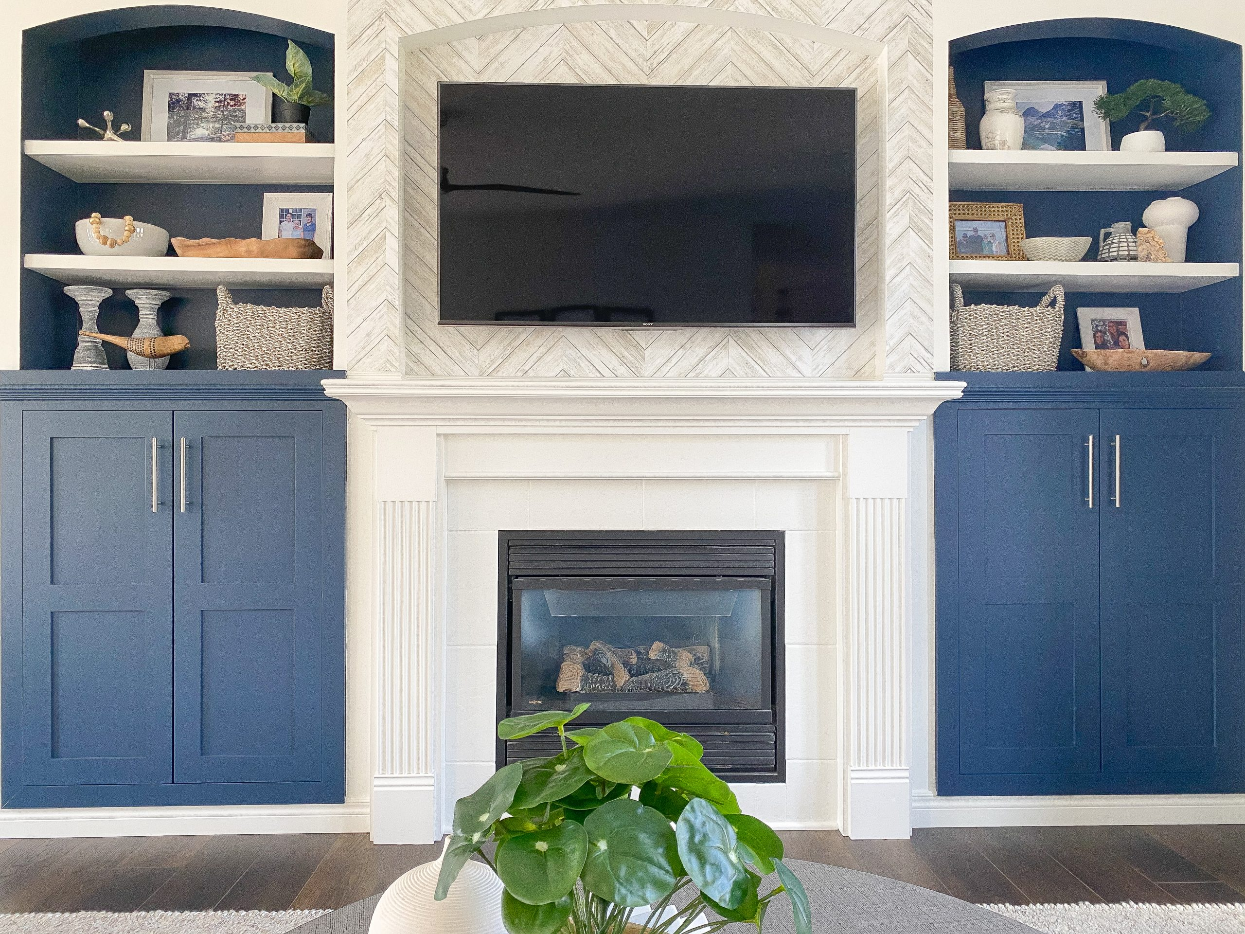 Interior designer in Chatham Ontario transforms a fireplace and mantle with colour, wallpaper, and styled shelves.