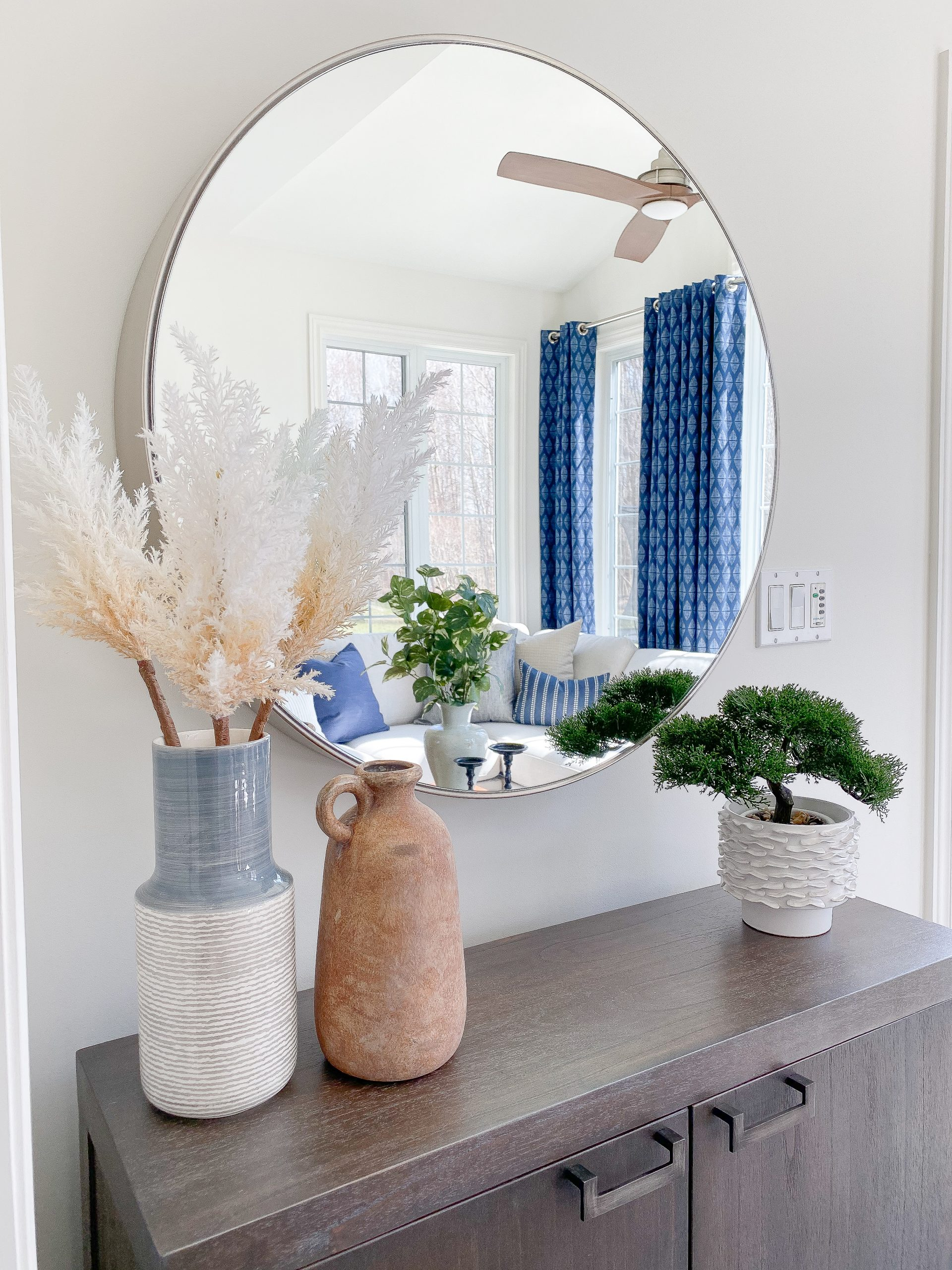 Interior decorator in Chatham Ontario styles a console table with colourful accessories