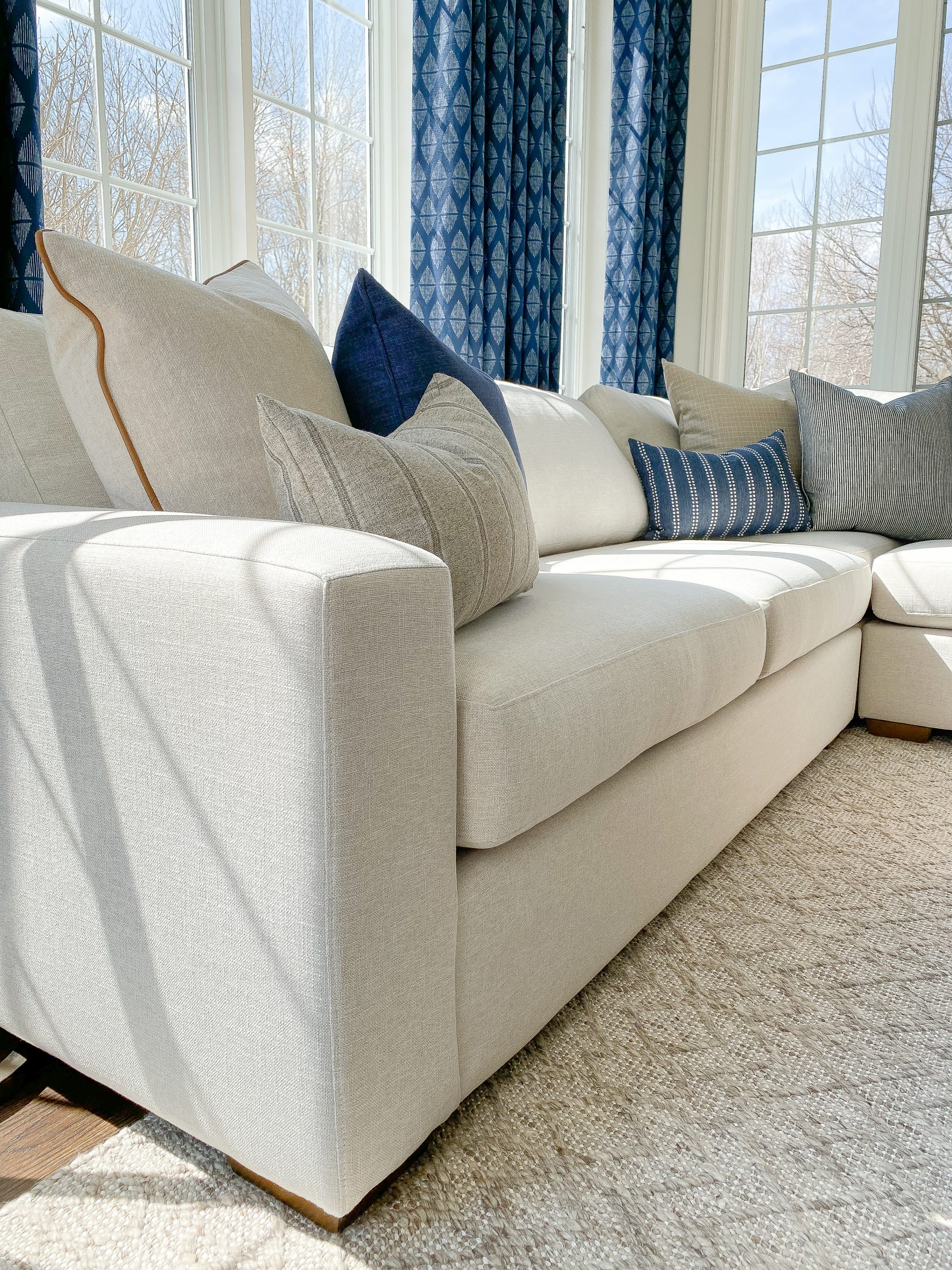 Interior designer in Chatham Ontario reveals a transitional lakeside retreat with modern sectional, custom drapery, and colourful pillows