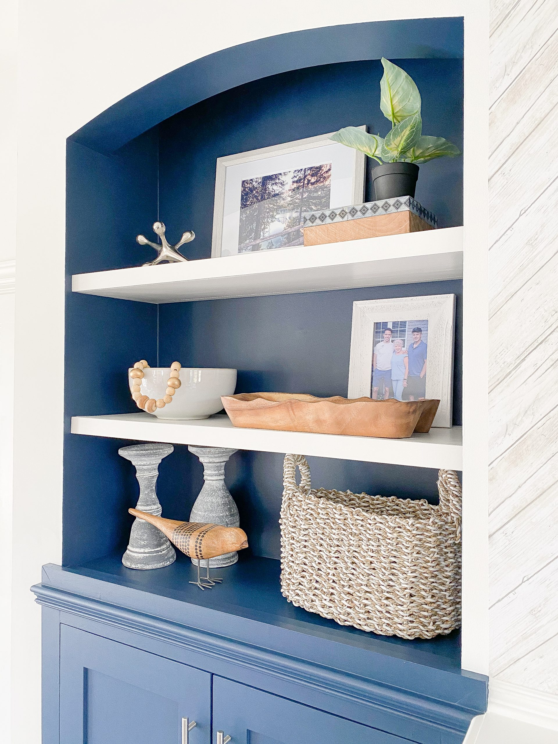 Styling a bookshelf with wood and wicker accessories at a lakeside retreat in Chatham Ontario